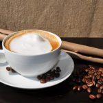 Ein Capuccino mit Kaffeebohnen daneben