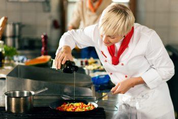 Eine Köchin bereitet eine Gemüsepfanne zu