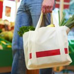Mann trägt volle Einkaufstasche mit Obst und Gemüse
